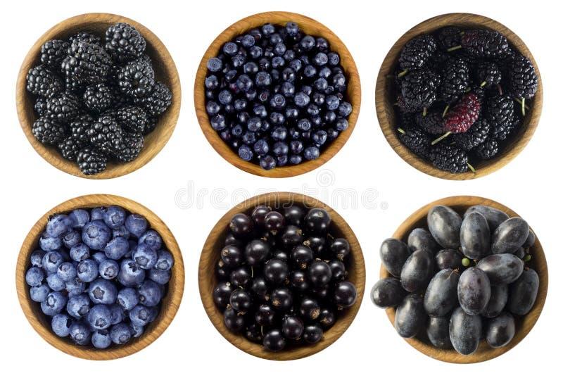 Zwarte en blauwe bessen op een witte achtergrond Braambessen, blackcurrants, bosbessen, moerbeibomen en druiven in een houten kom royalty-vrije stock foto's