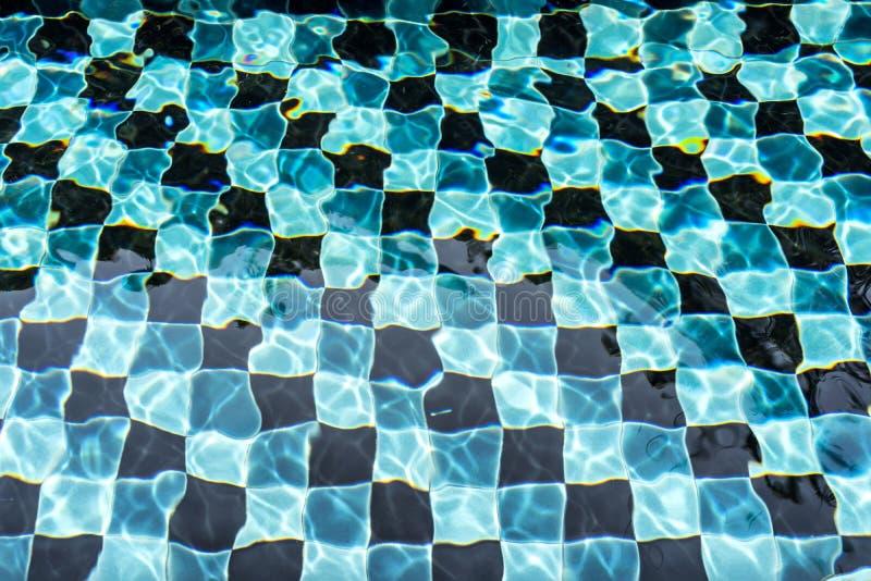 Zwarte en blauwe mozaïekvloer van zwembad in daglicht stock foto