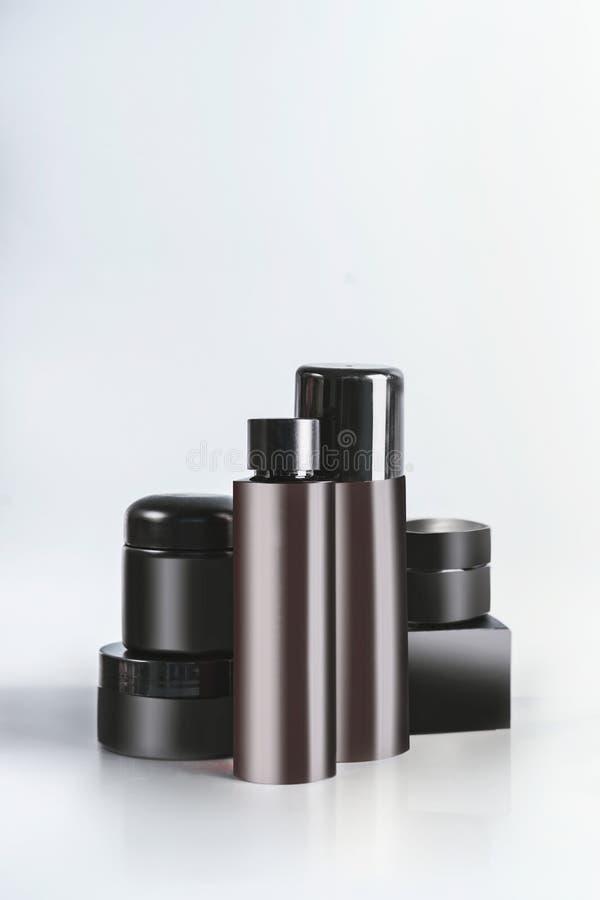 Zwarte en bruine cosmetische productkruiken en flessen met het brandmerken van spot die omhoog, zich op lichte lijst bij muuracht stock foto's