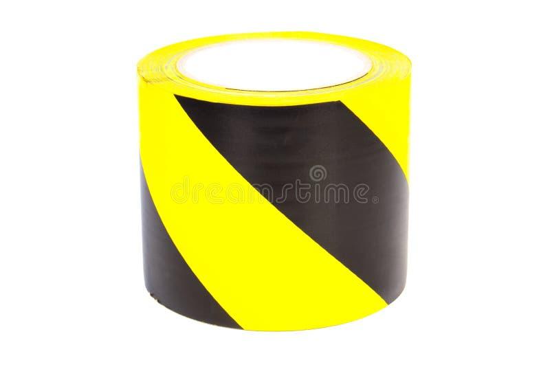 Zwarte en gele waarschuwingsband op witte achtergrond stock foto