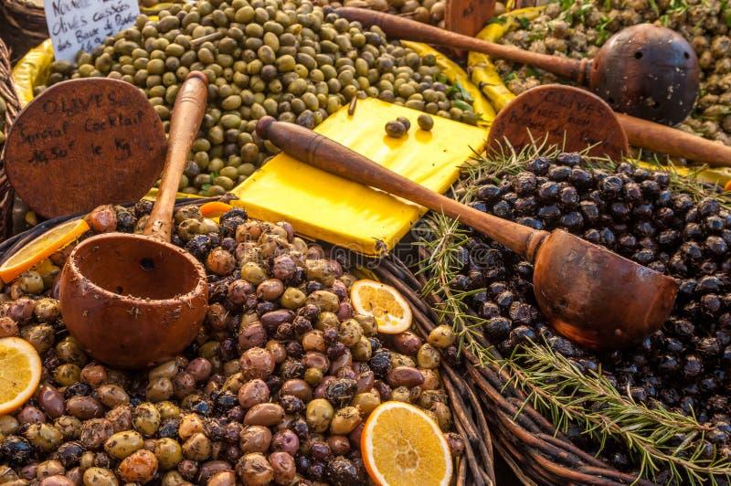 Zwarte en groene olijven met kruiden en houten lepels op Fransen stock afbeelding