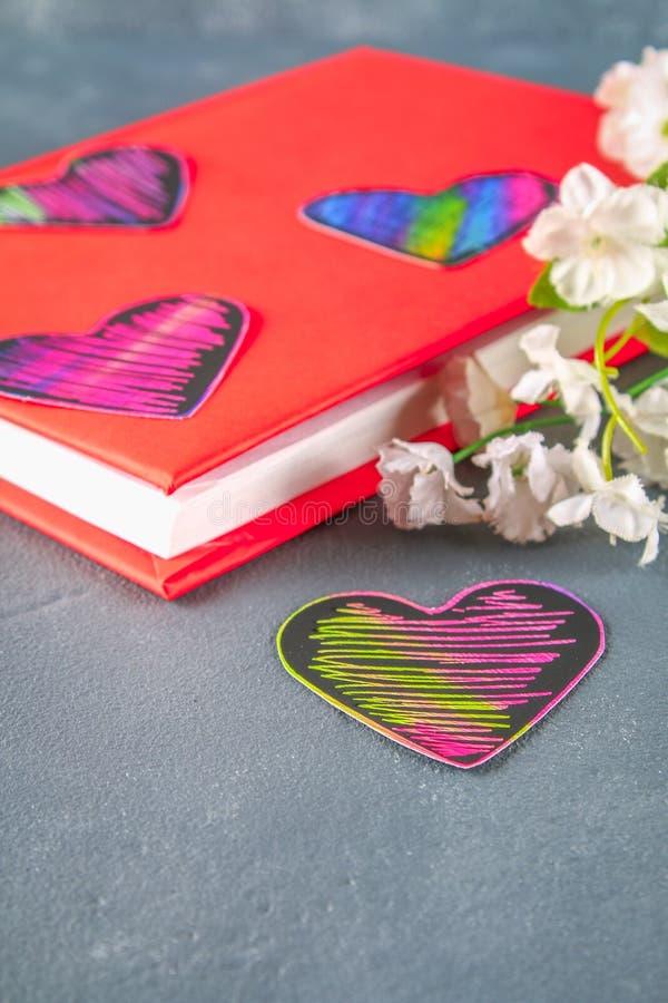 Zwarte en roze harten op een boek in een rode dekking en bloemen op een grijze concrete achtergrond Het concept de Dag van Valent stock foto's