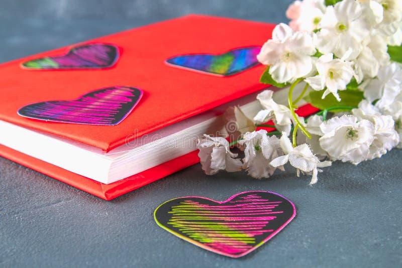 Zwarte en roze harten op een boek in een rode dekking en bloemen op een grijze concrete achtergrond Het concept de Dag van Valent royalty-vrije stock foto