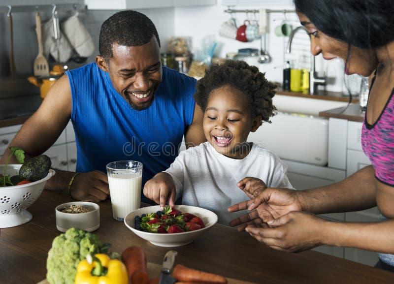 Zwarte familie die gezond voedsel samen eten stock afbeeldingen
