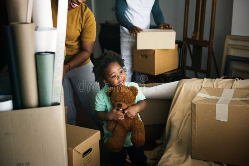 Zwarte familie die zich binnen aan hun nieuw huis bewegen stock afbeeldingen
