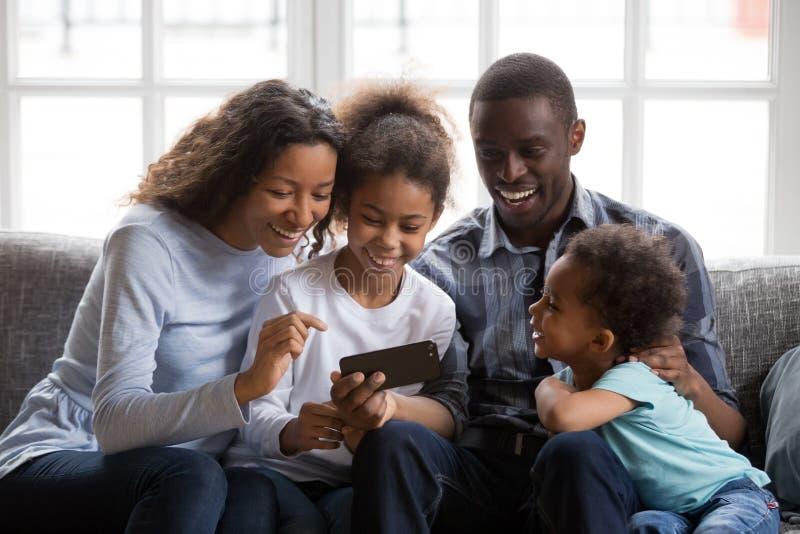 Zwarte familie en jonge geitjes het lachen het letten op grappige video op telefoon stock foto's