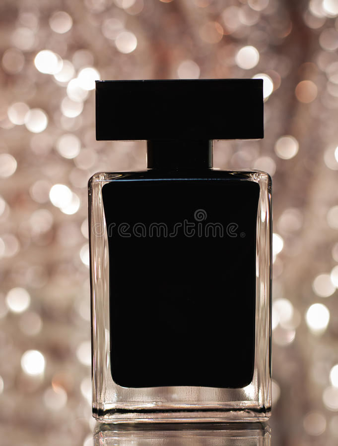 Zwarte fles parfum over roze bokeh royalty-vrije stock fotografie