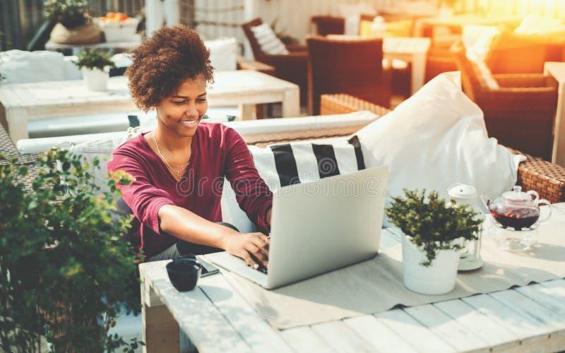 Zwarte freelancervrouw met laptop in straatbar stock fotografie
