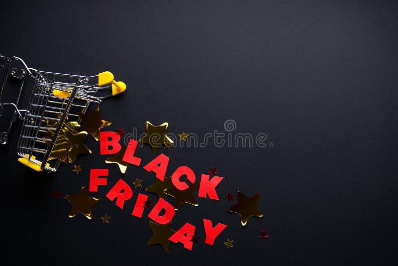 Zwarte friday-concept Gele trolley met veelkleurige confetti op een zwarte achtergrond, hoogste mening, plaats voor tekst stock afbeeldingen