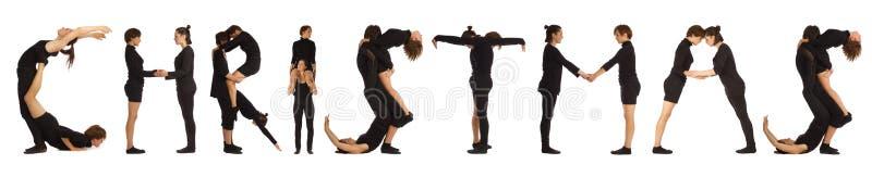 Zwarte geklede mensen die KERSTMISwoord vormen stock afbeelding