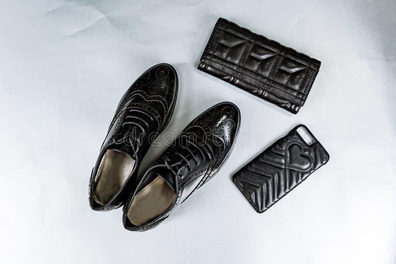 Zwarte geperforeerde schoenenoxfords, een beurs en een telefoongeval op een document witte achtergrond royalty-vrije stock fotografie