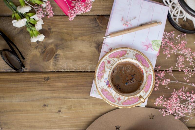 Zwarte geurige koffie, bloemen en glazen Goedemorgen, heldere zonnige kleuren Vrouwen` s toebehoren en blocnote met een pen stock afbeelding