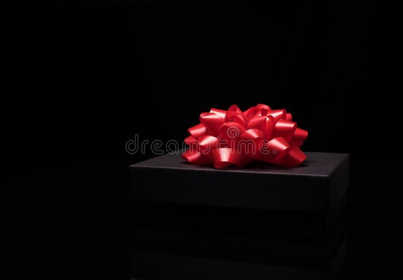 Zwarte giftdoos op een zwarte oppervlakte met grote rode boog royalty-vrije stock fotografie