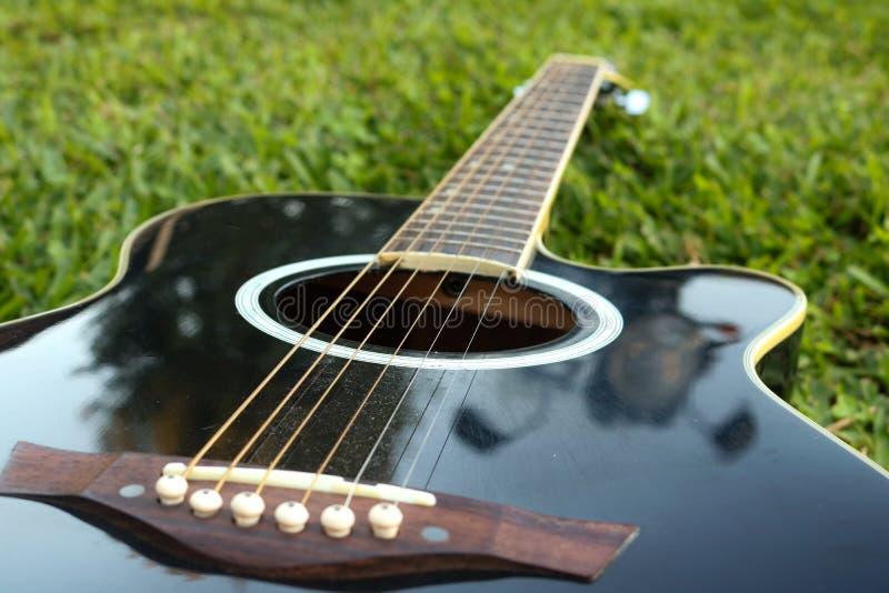 Zwarte gitaar die op het groene gazon met een nadruk op de koorden liggen stock foto's