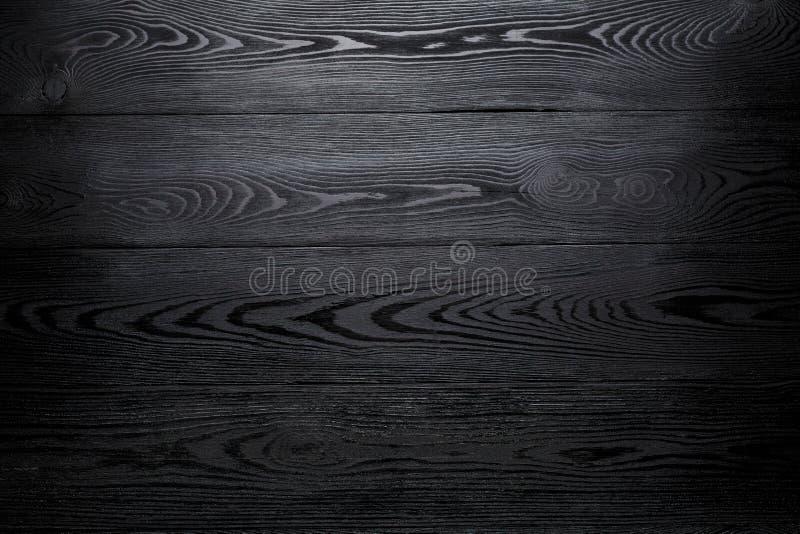 Zwarte glanzende houten abstracte achtergrond met het verdonkeren bij de randen stock afbeeldingen
