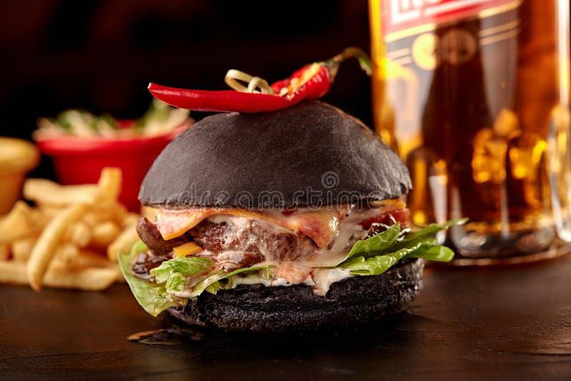 Zwarte grote sandwich - zwarte hamburger met sappige rundvleeshamburger, kaas, tomaat, en rode ui op lijst royalty-vrije stock fotografie