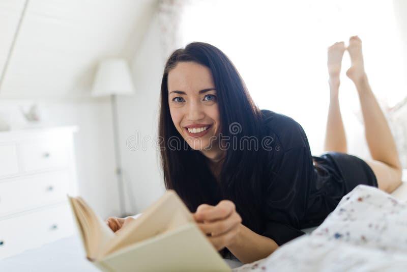 Zwarte haired vrouwennachtkleding die op bed leggen stock foto