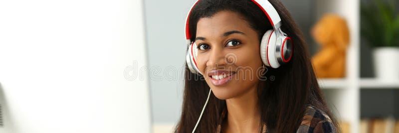 Zwarte het glimlachen vrouwenzitting op het werk die hoofdtelefoons dragen royalty-vrije stock afbeeldingen