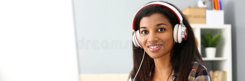 Zwarte het glimlachen vrouwenzitting op het werk die hoofdtelefoons dragen stock foto