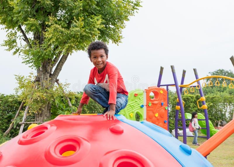 Zwarte het jonge geitjejongen die van Amerikanen pret op kinderen ` s hebben te spelen climbin stock foto