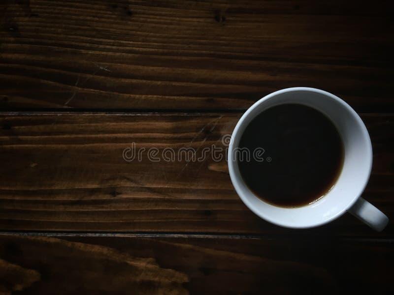 Zwarte hete koffie in kop hoogste mening over houten lijstachtergrond royalty-vrije stock fotografie