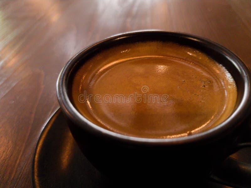 Zwarte hete koffiemok op de houten foto van het vloerclose-up royalty-vrije stock foto
