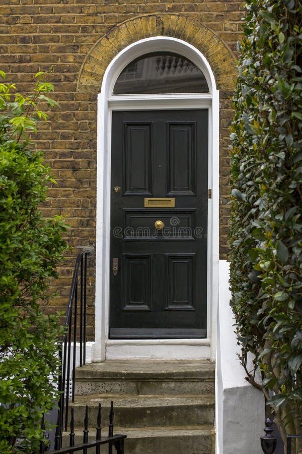 Zwarte Houten Ingangsdeur aan woningbouw in Londen Typische deur in de Engelse stijl royalty-vrije stock afbeeldingen