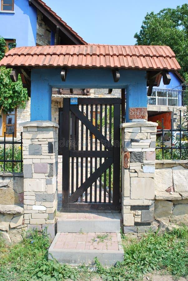 Zwarte houten poort, rode tegel, wilde steen, blauwe kolom royalty-vrije stock afbeelding