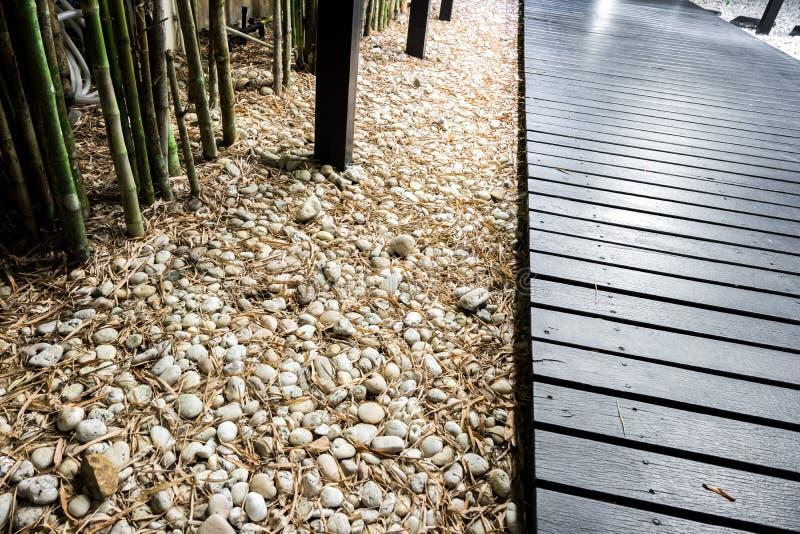 Zwarte houten tuinweg op witte kiezelstenen met bamboe stock afbeelding
