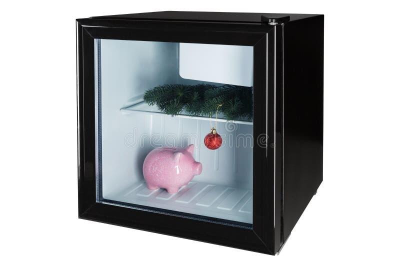 Zwarte ijskast met gesloten glasdeur, binnen de ijskast van de pijnboomtak, de Kerstmisdecoratie en roze piggy stock fotografie