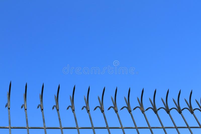 Zwarte ijzer scherpe omheining op blauwe hemelachtergrond royalty-vrije stock afbeeldingen