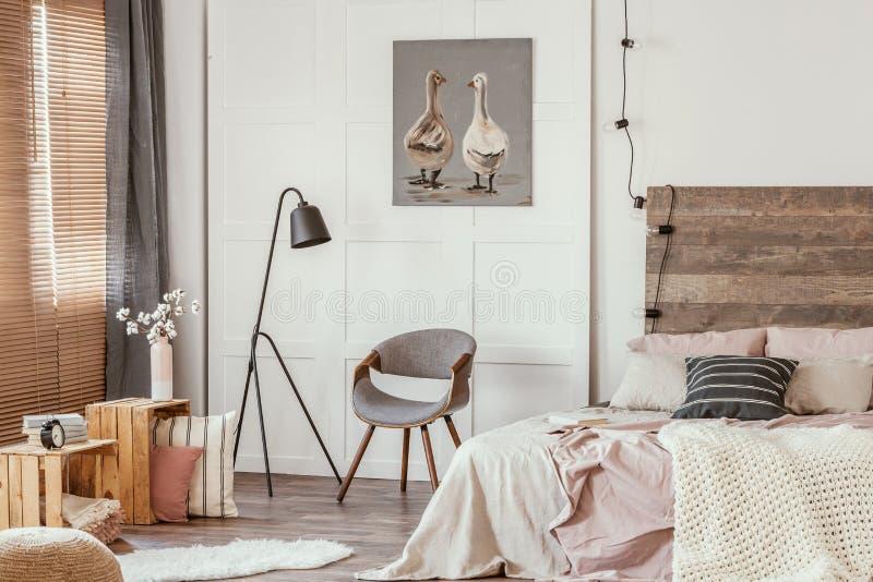 Zwarte industriële lamp naast een stijlvolle grijze houten stoel in het midden van een prachtige slaapkamer binnenshuis stock afbeeldingen