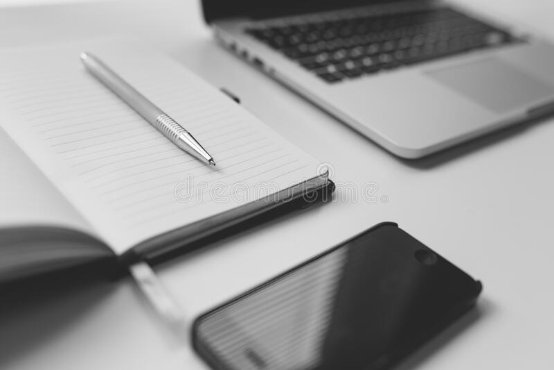 Zwarte Iphone naast Zilveren Pen op Wit Notitieboekje dichtbij Laptop Computer op Lijst royalty-vrije stock foto