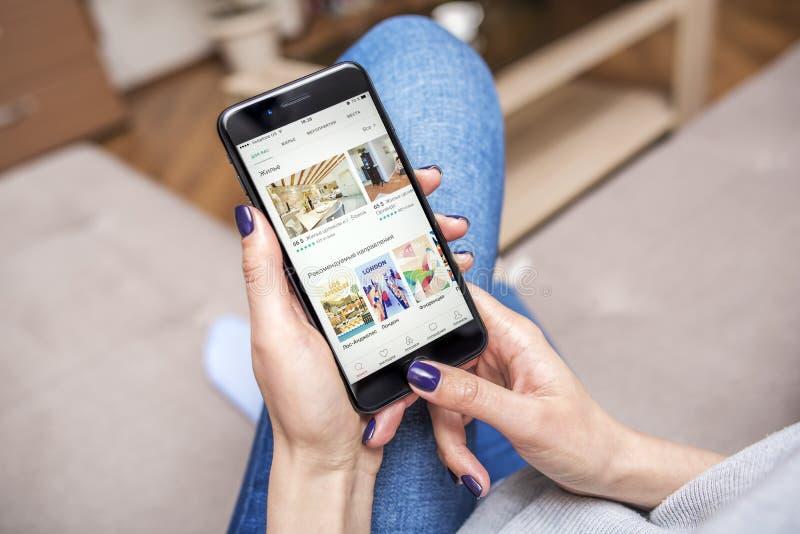 Zwarte iPhone 7 plus met Airbnb, app voor het boeken van flats en hotels in handen stock afbeelding
