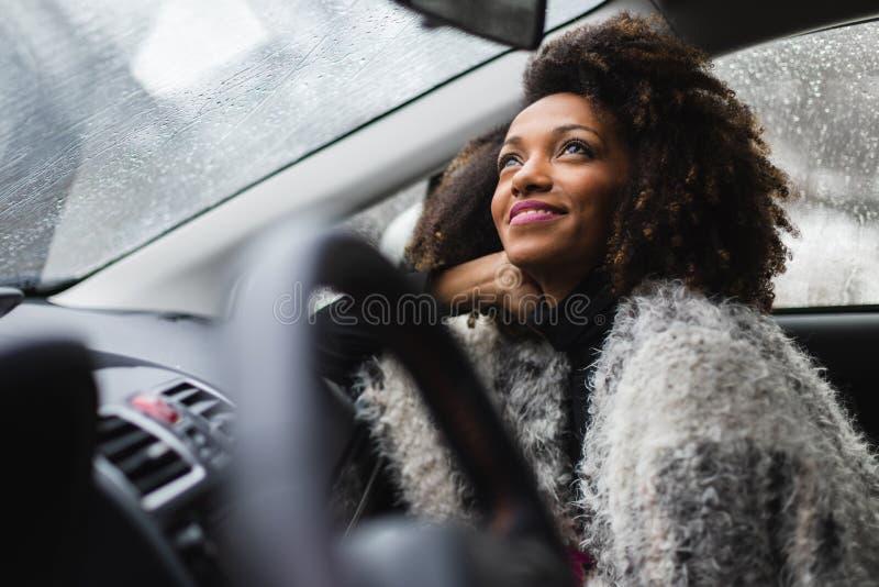 Zwarte jonge vrouw binnen een auto in de winter terwijl zijn het regenen stock afbeeldingen