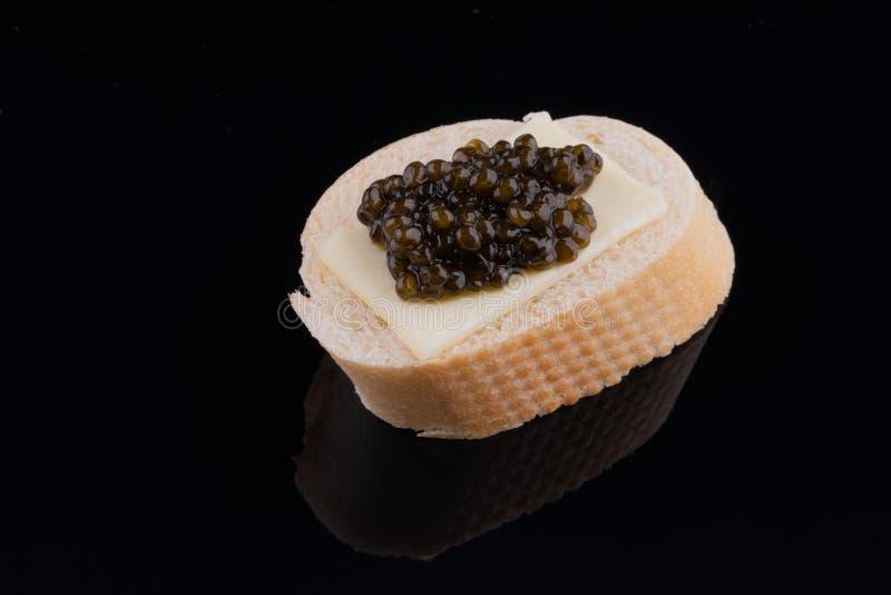Zwarte kaviaar op verse baguette met boter, zwarte spiegelachtergrond Close-up royalty-vrije stock foto
