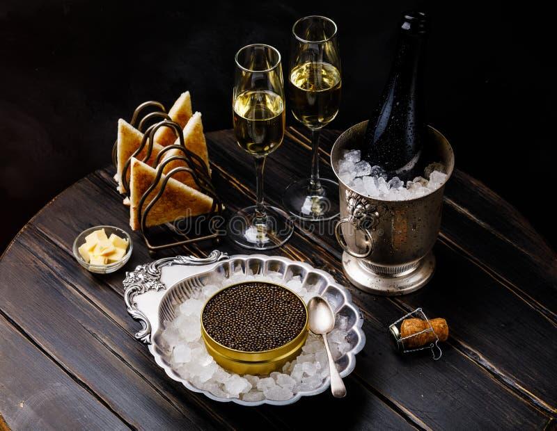 Zwarte kaviaar in zilveren kom, verse broodtoost en champagne stock foto's