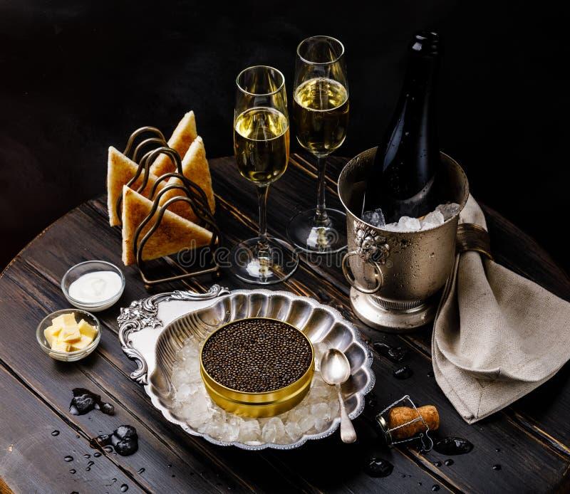 Zwarte kaviaar in zilveren kom, verse broodtoost en champagne stock fotografie