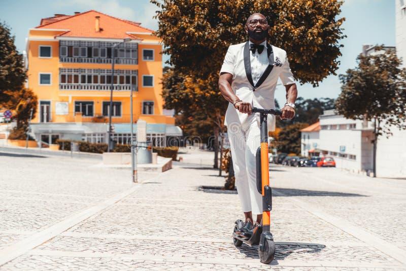 Zwarte kerel die e-autoped in openlucht met behulp van royalty-vrije stock afbeeldingen