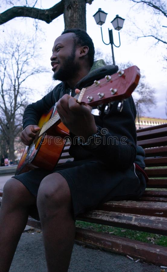Zwarte kerel die een gitaar spelen en gelukkige zitting in een bank van een park zingen stock fotografie