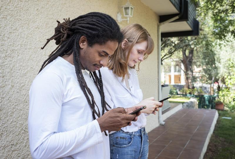 Zwarte kerel en Kaukasisch meisje die en met de celtelefoon letten op babbelen royalty-vrije stock foto's