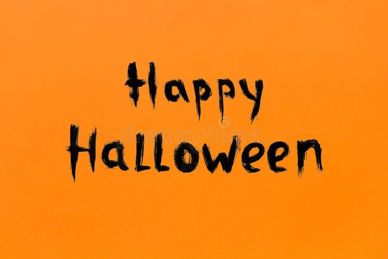 Zwarte kleur van Halloween van de tekstinschrijving de Gelukkige op oranje achtergrond stock foto