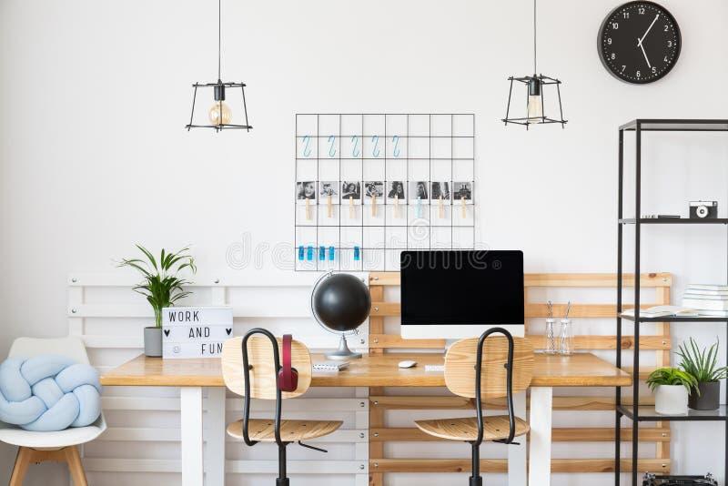 Zwarte klok in wit bureau royalty-vrije stock afbeelding