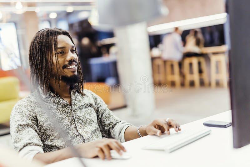 Zwarte knappe ontwerper die zijn werk aangaande een computer doen stock foto's