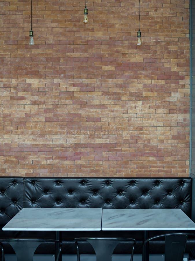Zwarte knoop-doorgenaaide lange retro stijlbank en marmeren eettafel in restaurant op bakstenen muurachtergrond royalty-vrije stock foto