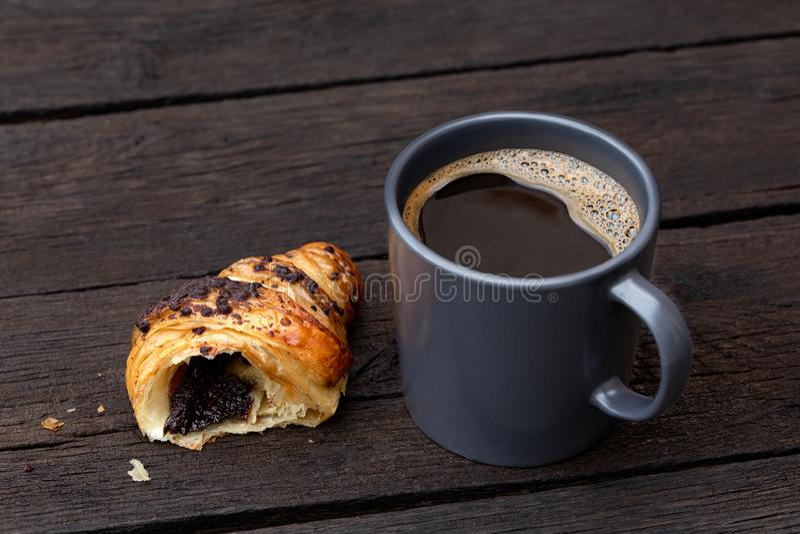 Zwarte koffie in een blauw-grijze ceramische mok naast de helft van chocoladecroissant die op rustieke donkere bruine houten lijs stock fotografie