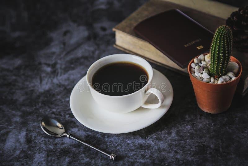 Zwarte koffie in een witte die koffiekop en een cactus op een zwarte achtergrond wordt geplaatst stock fotografie