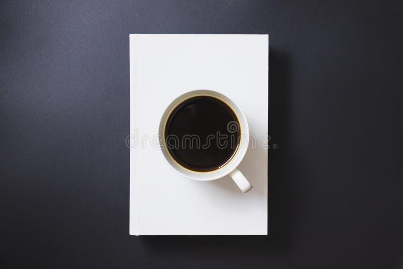 Zwarte koffie in een witte die koffiemok op witte boeken wordt geplaatst royalty-vrije stock foto