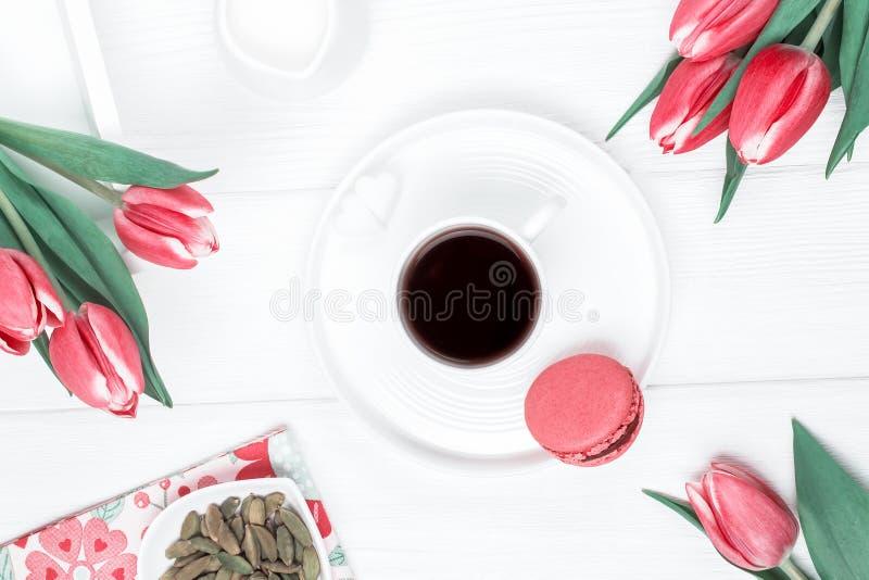 Zwarte koffie in een witte kop, een kardemom, rode tulpen en een framboos macaron of een makaron op een houten achtergrond Hoogst stock foto
