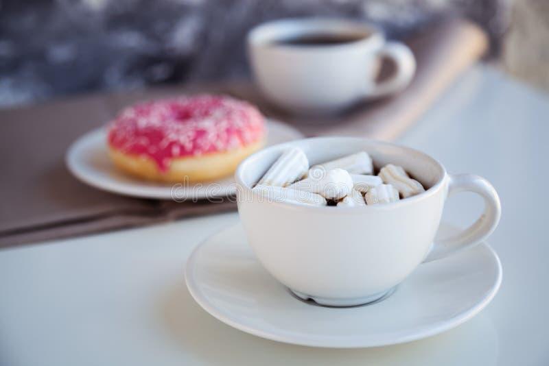 Zwarte koffie met verglaasde doughnut stock fotografie